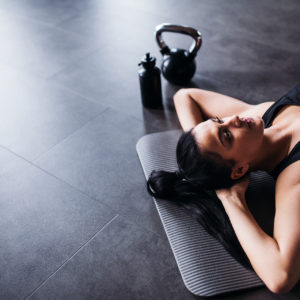 Woman ready for personal training session laying on yoga mat